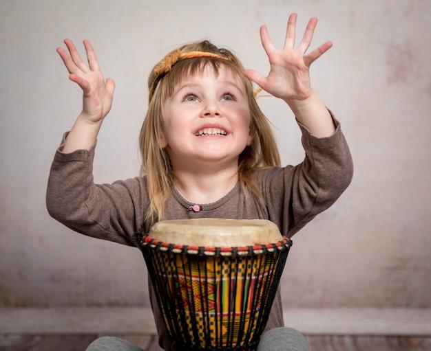 Niña linda tocando el tambor