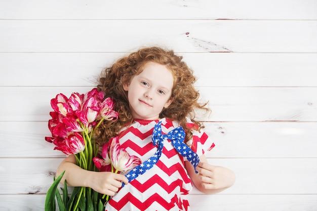 Niña linda con los tulipanes rojos en la celebración del 4 de julio. concepto de día de la independencia.