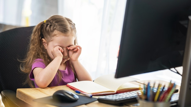 Niña linda usando una computadora para e-learning remoto se frota los ojos