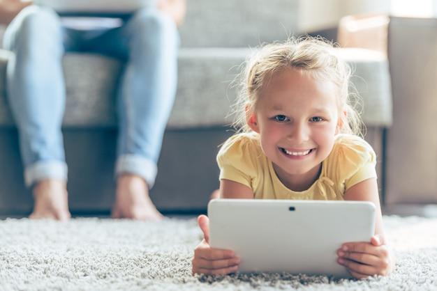 Niña linda está usando tableta digital, mirando a cámara.