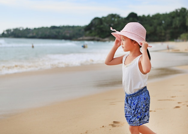 Niña linda usar sombrero de paja caminando en la playa a6f3c8bf484