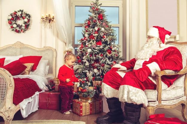 Niña linda con un verdadero santa claus cerca del árbol de navidad.
