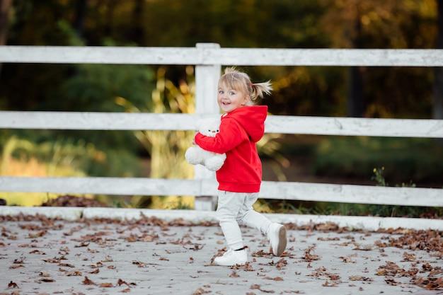 Niña linda vestida con ropa deportiva roja en el parque de otoño, jugando con un oso de peluche en un día soleado