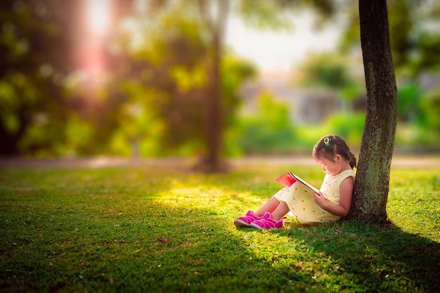 Una niña linda en un vestido amarillo leyendo un libro sentado bajo el árbol