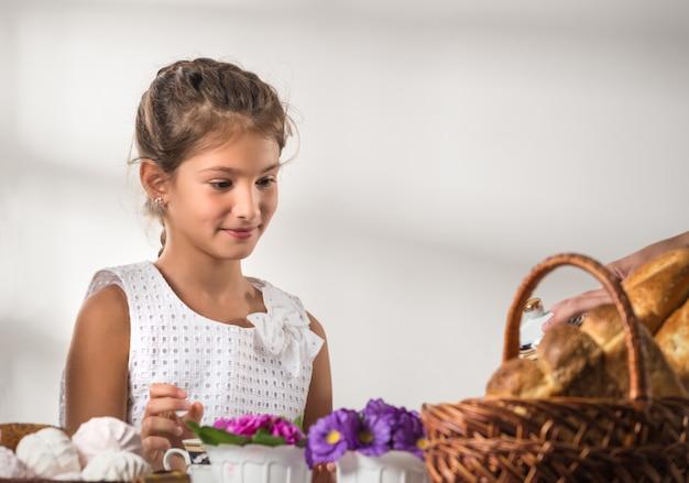 Niña linda en un vestido blanco bebe té