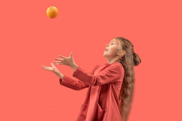 Niña linda en vestido coral con cabello largo jugando con una naranja