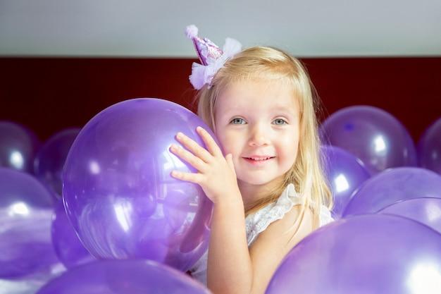Niña linda en vestido elegante que celebra el día de cumpleaños con globos púrpuras