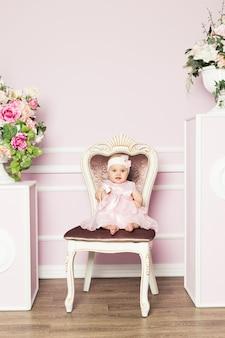 Niña linda en vestido de moda con flores de primavera