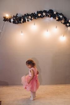 Una niña linda con un vestido con el pelo rizado mira su vestido cerca de la guirnalda