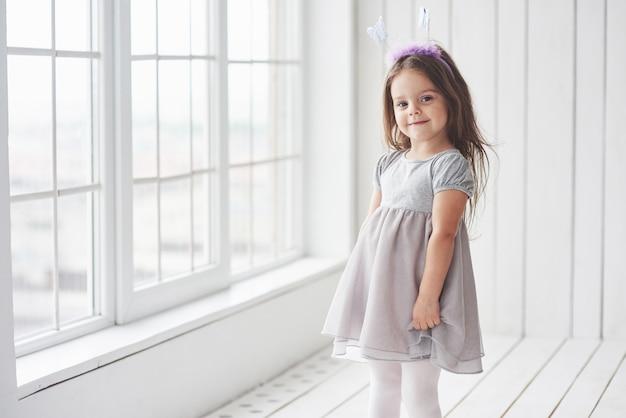 Niña linda en vestido de pie en la habitación blanca cerca de las ventanas.