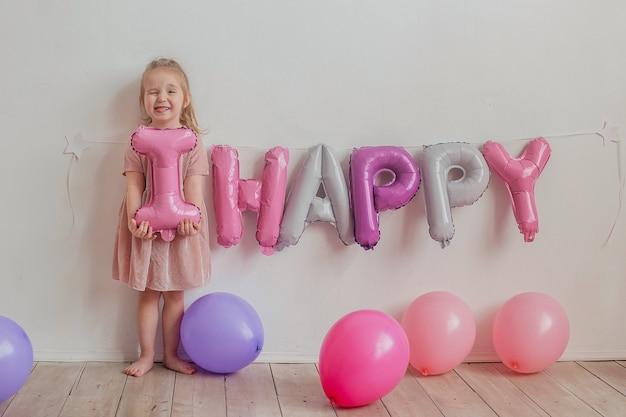 Niña linda en un vestido rosa posa frente a la cámara, niño feliz sonriente muestra lengua. cumpleaños infantil.