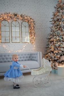 Niña con lindo vestido y diadema, lleva el cochecito en la habitación decorada festivamente con guirnalda de luces.