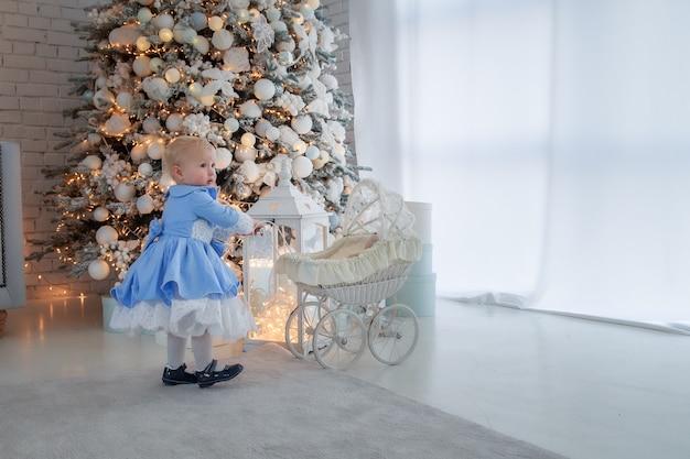 Niña con lindo vestido y diadema lleva cochecito en sala decorada festivamente