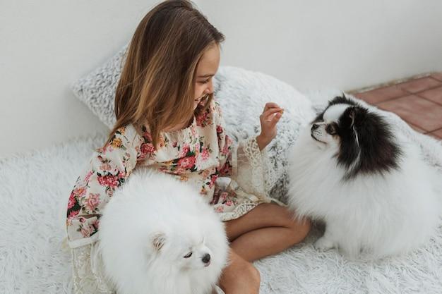 Niña y lindos cachorros blancos sentados en la cama