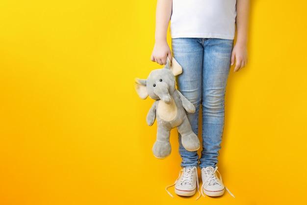 La niña está lista para viajar. piernas de una niña en ropa casual en jeans y una camiseta blanca con un juguete en la mano sobre un amarillo