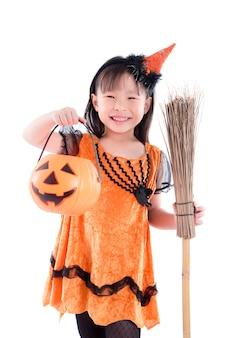 Niña, llevando, bruja, disfraz de halloween, posición, con, escoba, encima, fondo blanco
