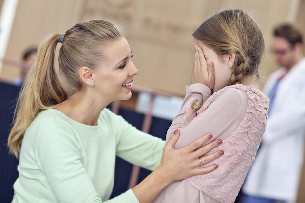 Niña llorando mientras está con su madre en un médico en consulta
