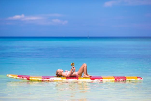 Niña con lollipop divertirse en tabla de surf en el mar