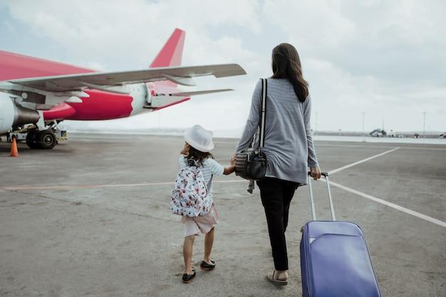 Niña y madre cogidos de la mano caminan hacia el avión