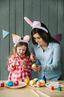 Niña y madre felices en orejas de conejo pintando huevos para pascua