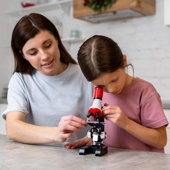 Niña y madre haciendo experimentos con microscopio.