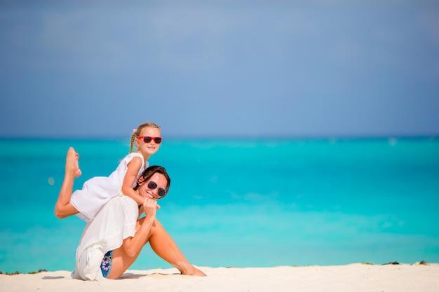 Niña y madre joven durante vacaciones en la playa