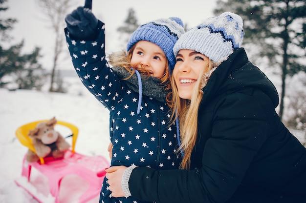 Niña con madre jugando en un parque de invierno
