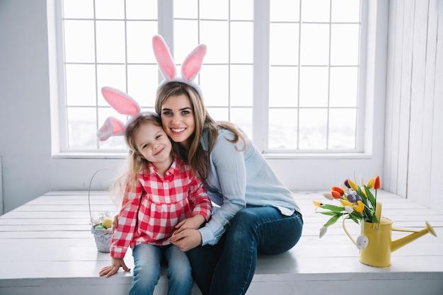 Niña y madre en orejas de conejo sentadas cerca de canasta con huevos de pascua