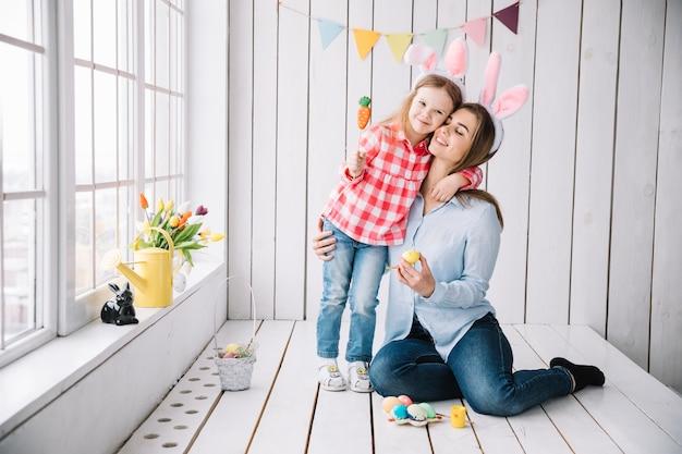 Niña y madre en orejas de conejo sentado con huevos de pascua