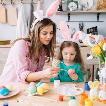 Niña con madre pintando huevos para pascua en mesa