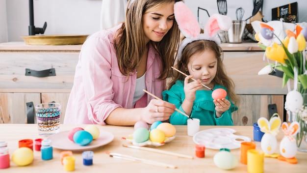 Niña con madre pintando huevos para pascua