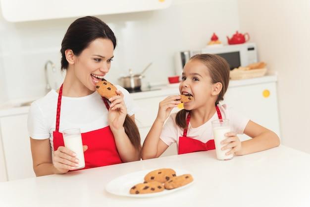 La niña y la madre prueban las galletas en la cocina.