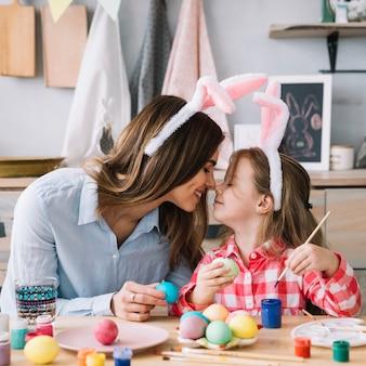 Niña y madre tocando narices mientras pintan huevos para pascua