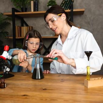 Niña y maestra haciendo experimentos científicos con microscopio