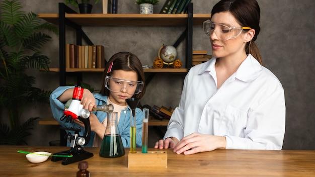 Niña y maestra haciendo experimentos científicos con tubos de ensayo y microscopio