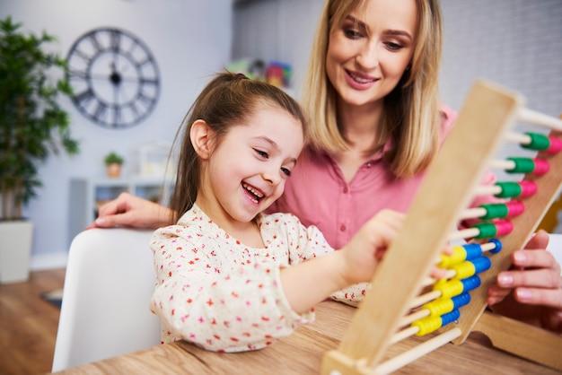 Niña y maestra usando un ábaco durante la educación en el hogar