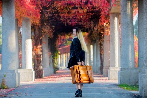Niña con maleta en callejón de uvas rojas