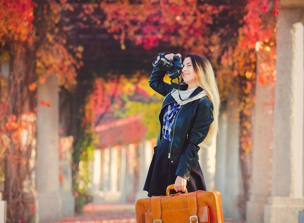 Niña con maleta y cámara en callejón de uvas rojas