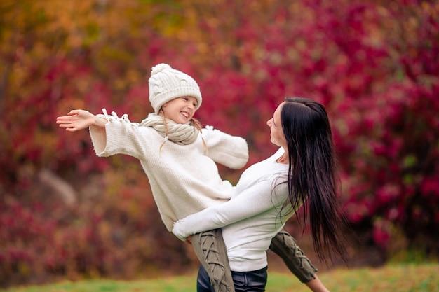Niña con mamá al aire libre en el parque en día de otoño