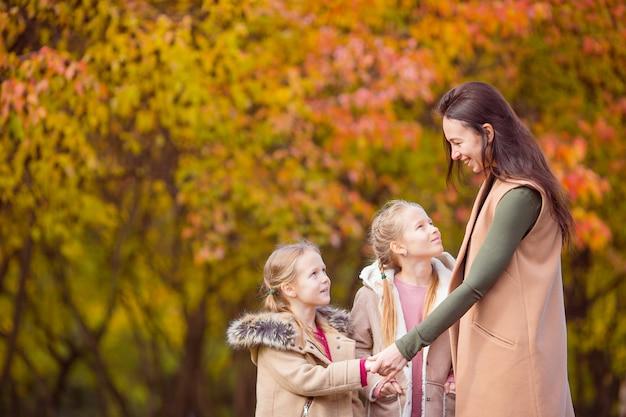 Niña con mamá al aire libre en el parque en el día de otoño