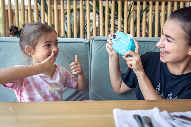 Niña, mamá y una cámara digital de juguete para niños para impresión fotográfica instantánea.