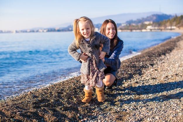 Niña con mamá divirtiéndose en la playa en un día de invierno