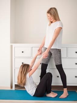 Niña y mamá en el entrenamiento en casa