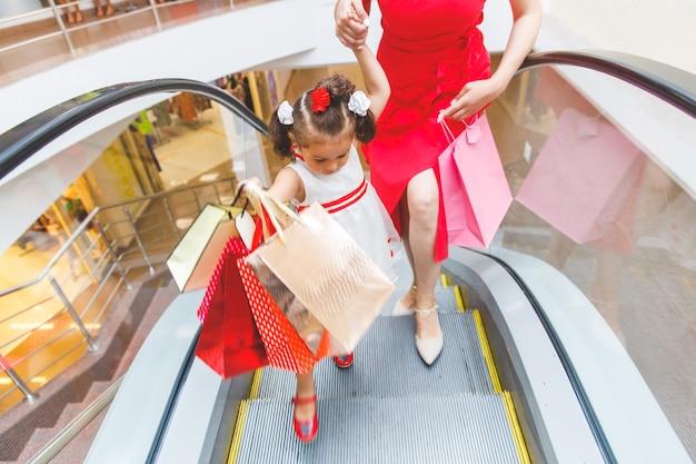 Niña con mamá en la escalera mecánica en el centro comercial con compras