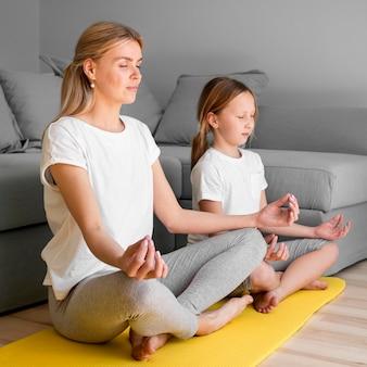 Niña y mamá meditando