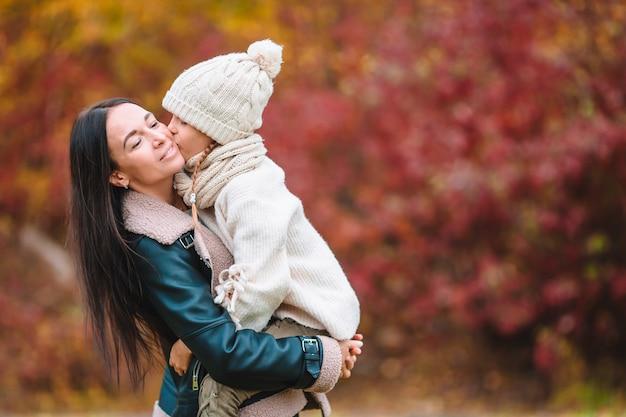 Niña con mamá en el parque en día de otoño