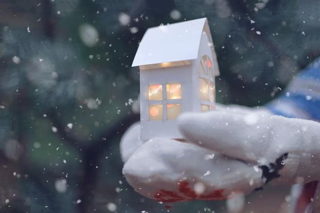 Niña en manopla sosteniendo una casa de papel con luz de navidad
