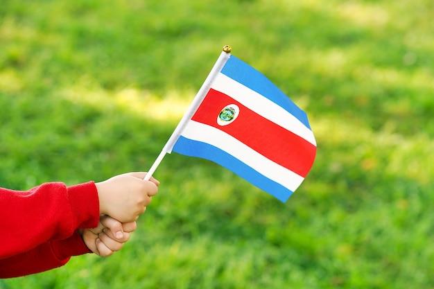 Niña manos sostienen la bandera de costa rica