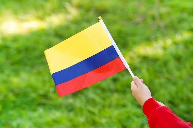Niña manos sostienen la bandera de venezuela