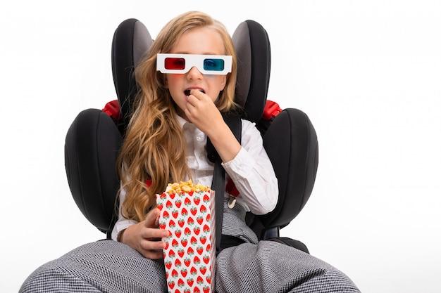 Una niña con maquillaje y cabello largo y rubio se sienta en la silla del bebé del automóvil y se ve película o dibujos animados con palomitas de maíz aislado en blanco